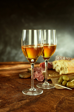 sherry: Profile Still Life of Two Glasses of Warm Sherry Wine in front of Cured Meats, Olives and Loaf of Bread on Rustic Wooden Bread