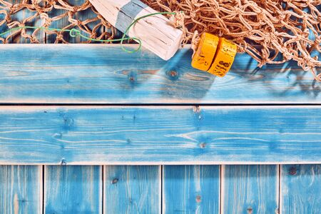 waif: Nautical Themed Background with Copy Space - High Angle Still Life of Blue Painted Wood Planks with Natural Rope Fishing Net and Buoy