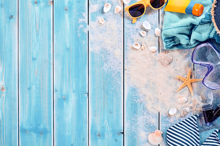 Sommarlovet vattensporter bakgrundstema med snäckskal, lös sand, solglasögon, simning kläder och undervattensglasögon över ridit trä blå bakgrund med kopia utrymme Stockfoto