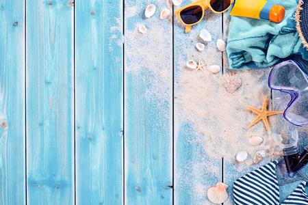 Zomervakantie watersport achtergrond thema met schelpen, los zand, zonnebrillen, zwemkleding en onderwater bril op verweerd hout blauwe achtergrond met kopie ruimte Stockfoto