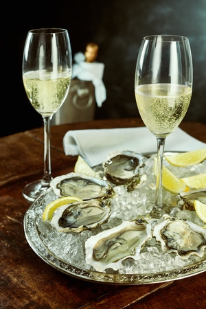 brisk: Pair of tall glasses of champagne next to silver platter of oysters and lemon slices on table with cooler and napkin in background Stock Photo