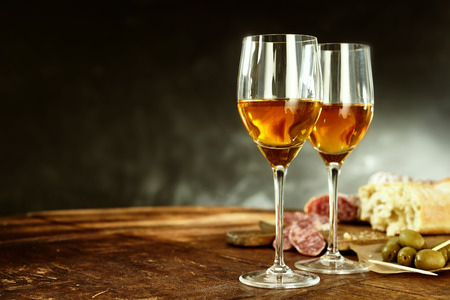 fortified: Two glasses of sherry served with tasty traditional Spanish tapas of olives, salami and fresh bread on an old wooden table with copy space
