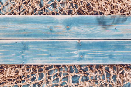 natural rope: High Angle Still Life of Planks of Blue Painted Wood Horizontal Through Center of Frame and Overlay on Natural Rope Fishing Net - Nautical Themed Background with Copy Space