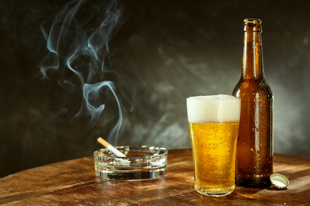 Burning cigarette in a glass ashtray and a long cold beer in a pint glass with bottle alongside served on an old wooden table in a pub