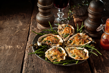 celeriac: Still Life View of Oysters Topped with Cheese Gratin on Platter with Greenery on Rustic Wooden Table with Salt and Pepper Mills and Copy Space