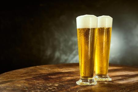 スレートの背景にコピー スペースを持つパブ、バーや居酒屋で昔の素朴な木製のテーブルの上に立ってエレガントな長いガラスの 2 つの氷冷泡ビー