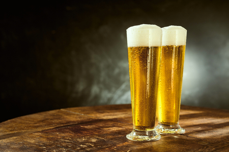 Two ice cold frothy beers in elegant long glasses standing on an old rustic wooden table in a pub, bar or tavern with copy space on a slate background Standard-Bild