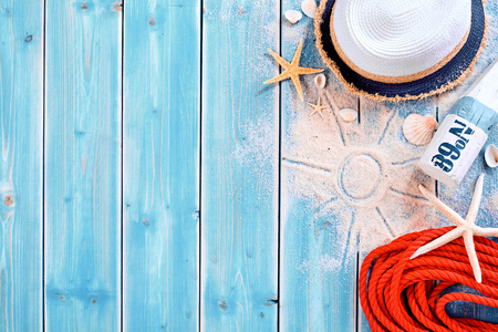 Summer vacation beach background theme with seashells, shape of sun in sand, red rope, sun tan bottle and hat with copy space over painted blue wood planks