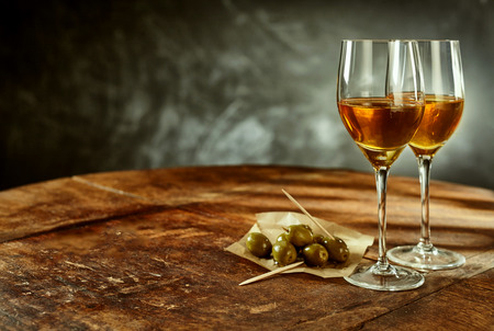 sherry: Profile Still Life of Two Glasses of Warm Sherry Wine on Rustic Wooden Table with Green Olives Appetizers with Copy Space