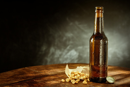 unlabelled: Profile View of Cold Bottle of Beer Covered in Condensation on Rustic Wooden Table with Cap and Peanuts, in Studio with Dark Background and Copy Space Stock Photo
