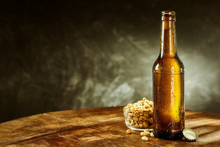 Open cold bottle of beer near a bowl full of peeled oily roasted peanuts on a round rustic wooden table