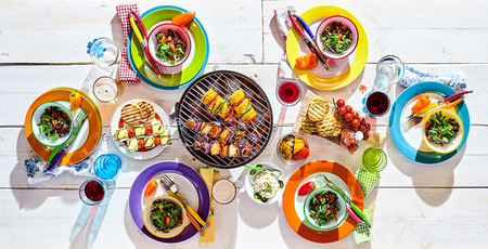 Overhead view of a colorful picnic table laid with multicolored plates, salad beverages and a BBQ with tofu kebabs for healthy vegetarian or vegan cuisine