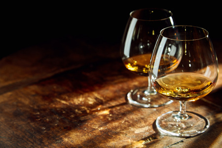 Sluit omhoog van twee bourbon gevulde glazen op houten lijst in een donkere ruimte met een paar stralen van zonlicht