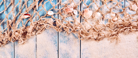 driftwood: Panoramic Nautical Themed Background with Sand, Net and Seashells on Blue Painted Wood Plank Background with Copy Space