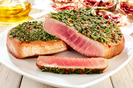tunny: Close Up Still Life of Seared Tuna Steaks Topped with Fresh Pesto and Served on Square White Plate on Painted Wooden Table Stock Photo