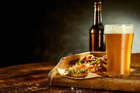 Vaso alto lleno de cerveza y una botella junto a las tapas envueltas en papel sobre la mesa de madera Foto de archivo - 56708353