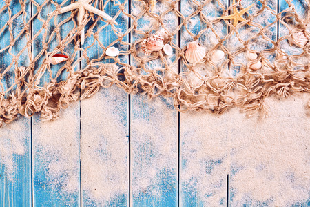 Nautical Themed Background with Copy Space - Fishing Net with Seashells and Sand Scattered on Blue Painted Wood Plank Background