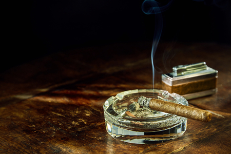 cheroot: Smoking cigar sitting in round glass ashtray besides fancy lighter on wooden table Stock Photo