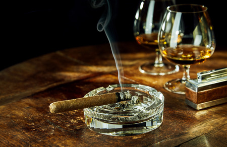 addictive drinking: Glass ashtray with smoking cigar by two glasses filled with bourbon besides fancy lighter on a wood table