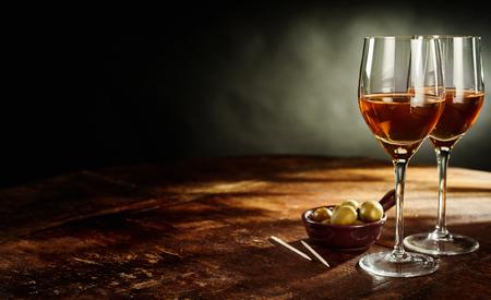 복사 공간이 녹색 올리브 전채와 소박한 나무 테이블에 여전히 따뜻한 셰리 와인 두 잔의 생활 프로필 스톡 콘텐츠