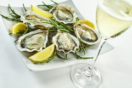 Open oyster shells with lemon wedges in plate with curled edges and drink in tall champagne glass over white Stockfoto
