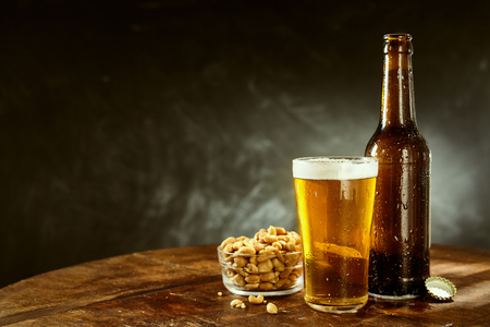 bar top: Beer served from a brown bottle into a long glass and a bowl of roasted salted peanuts on an old wooden bar table with copy space on slate behind