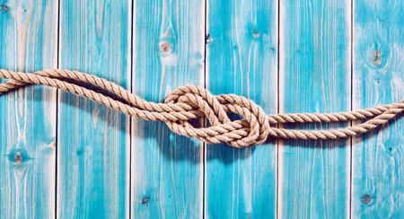 gefesselt: Nautischthemenorientiertes Hintergrund - Erhöhte Stillleben von Doppel Acht-Knoten in Natur Seil über Blau Holz bemalt Plank Hintergrund mit Textfreiraum Lizenzfreie Bilder