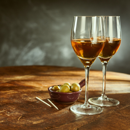 fortified: Profile Still Life of Two Glasses of Warm Sherry Wine on Rustic Wooden Table with Green Olives and Picks Stock Photo