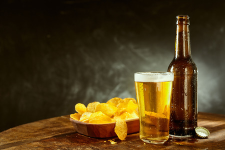 Cold beer in a long glass alongside an empty brown bottle and bowl of potato crisps on a bar counter with copy space