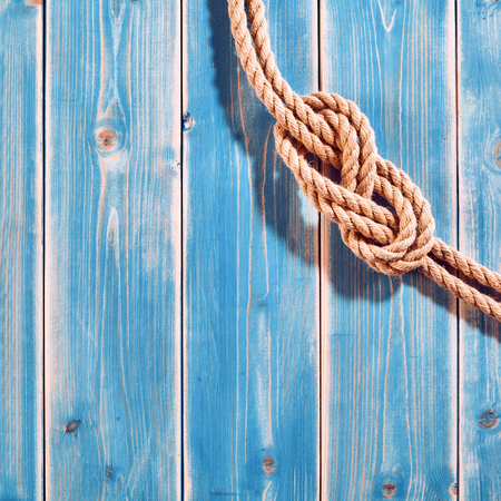 knot: Nautical Themed Background - High Angle Still Life of Double Figure Eight Knot in Natural Rope Across Corner of Blue Painted Wood Plank Background with Copy Space Stock Photo