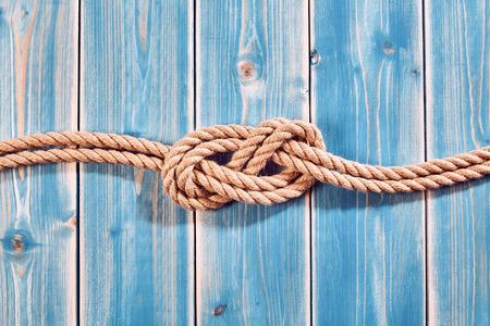 Nautischthemenorientiertes Hintergrund - Erhöhte Stillleben von Doppel Acht-Knoten in Natur Seil über Blau Holz bemalt Plank Hintergrund mit Textfreiraum