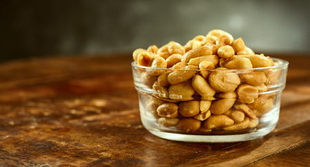 side bar: Glass bowl of fresh roasted salted peanuts or groundnuts on an old wooden table or bar counter in a side view with copy space