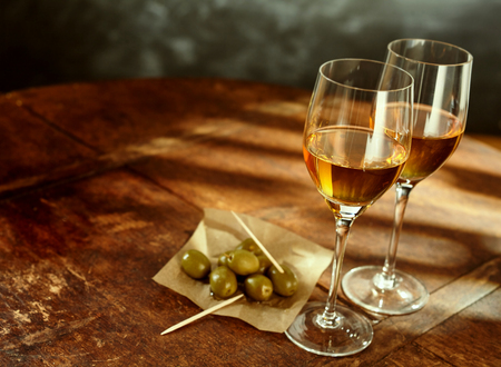 fortified: High Angle Still Life of Two Glasses of Warm Sherry Wine on Rustic Wooden Table with Green Olives and Picks