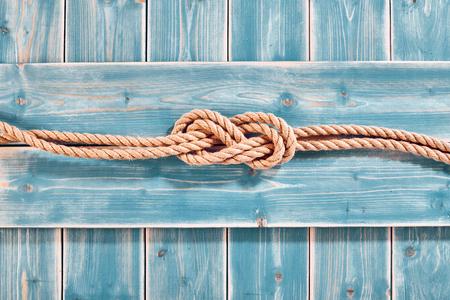 Nautischthemenorientiertes Hintergrund - Erhöhte Stillleben von Doppel Acht-Knoten in Natur Seil über Blau Holz bemalt Plank Hintergrund mit Textfreiraum Standard-Bild