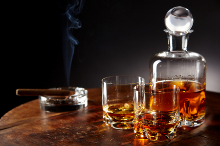 liquors: Decanter of alcohol by smoking cigar sitting in a round ashtray and two half filled glasses on a table in a dark room Stock Photo