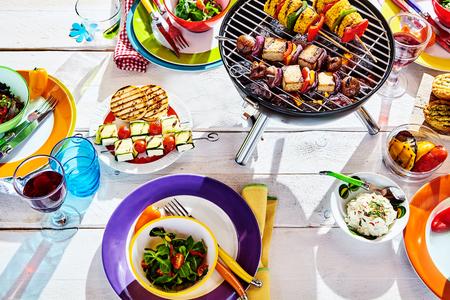 Overhead Goed aangelegd zomer tafel met kleurrijke gerecht en borden en koperslager op witte achtergrond met veganistische bbq spiesjes