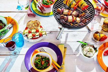well laid: Overhead Well Laid summer table with colorful dish and plates and brazier on white background with vegan bbq skewers