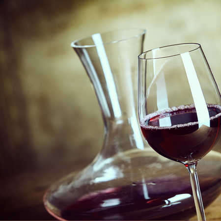 carafe: Glass of red wine with a stylish decanter behind in a close up view over an abstract brown background in square format