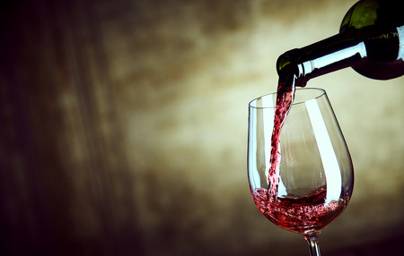 syrah: Serving a single glass of red wine from a bottle with a close up view of the neck of the bottle and glass over a wide angle abstract brown background with copy space