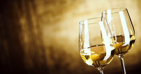 sauvignon blanc: Banner of Two glasses of white wine standing side by side in a close up view over a panoramic abstract brown background with copy space
