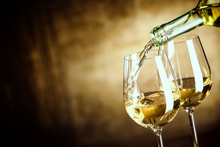 aperitif: Pouring two glasses of white wine from a bottle in a close up view of the wineglasses over an abstract brown blue background with copy space Stock Photo