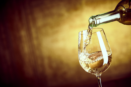 Banner of Pouring a glass of white wine from a bottle in a close up view on the elegant wine glass over a blurred brown background with copy space