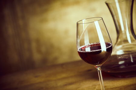 Single glass of red wine on a wooden table alongside a decanter or carafe with a rustic blurred brown background with copy space