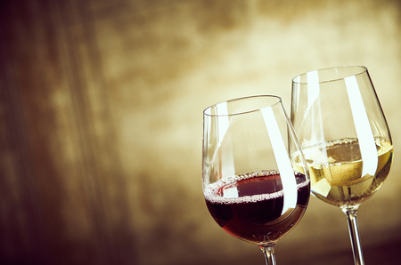 Wineglasses of red and white wine standing side by side in the corner over an abstract rustic brown background with copy space Stock Photo