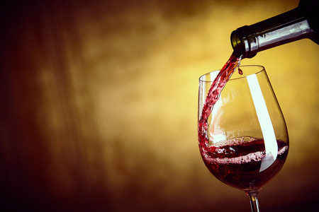 Pouring a single glass of red wine from a bottle in a close up view on the glass over an abstract brown background with copy space