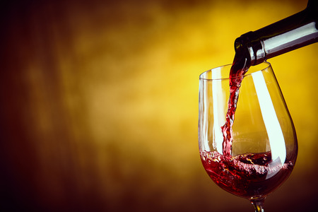 Serving a glass of red wine from a bottle with a close up view of the wine being poured into the bowl of an elegant wine glass over an abstract yellow brown background with copy space