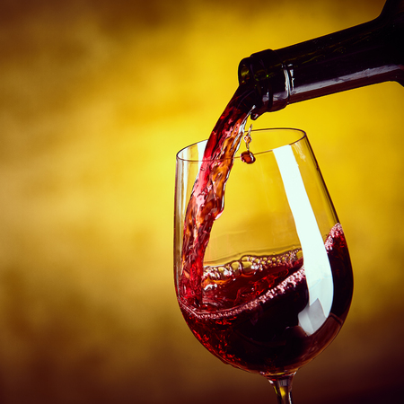 Dispensing red wine from a bottle into an elegant wineglass in a close up view on the liquid being poured over a blurred brown background, square format
