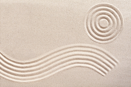 undulating: Undulating flowing wave pattern and concentric circles raked in the sand in a traditional Japanese zen garden for wellness and tranquility with copy space