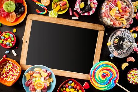 ブラック色の螺旋キャンディー ボウルや瓶、キャンディーと虹でカラフルな明るい各種お菓子の枠に囲まれた空白学校スレート