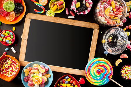 candy border: Blank school slate surrounded by a frame of colorful bright assorted candy in bowls and jars, candy canes and rainbow colored spiral lollipops on black